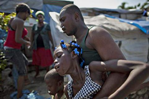 Refugees react to the effects of tear gas fired by police and UN soldiers during a protest in an area where displaced earthquake survivors live in Port-au-Prince, Haiti, 18 Nov. 2010