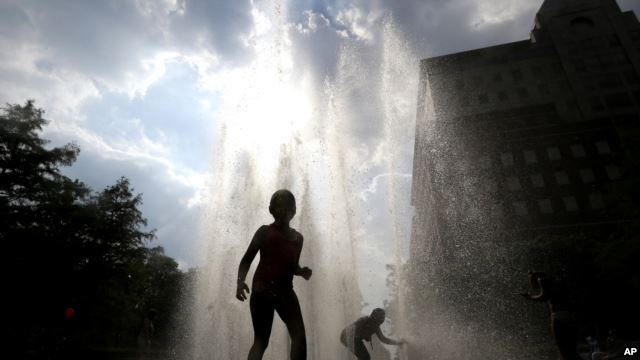 Children play in a fountain during a heat wave.